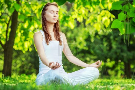 Photo pour Yoga outdoors. Woman meditating in lotus position zen gesturing. Concept of healthy lifestyle and relaxation - image libre de droit