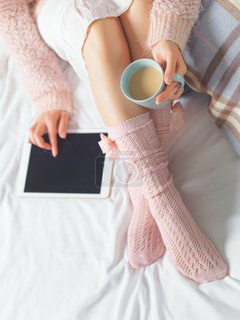 Photo pour Femme en utilisant une tablette à la maison confortable atmosphère sur le lit. Jeune belle femme appréciant le temps libre en utilisant un dispositif technologique, tenant une tasse de cacao ou de café. Lumière douce - image libre de droit