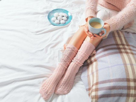 Photo for Woman relaxing at cozy home atmosphere on the bed. Young woman with cup of coffee or cocoa in hands and cookies enjoying comfort. Soft light and comfy lifestyle concept - Royalty Free Image