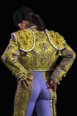 Woman bullfighter posing suit on his back with light purple and gold with sword