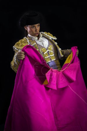 Woman bullfighter holding capote pink on black background
