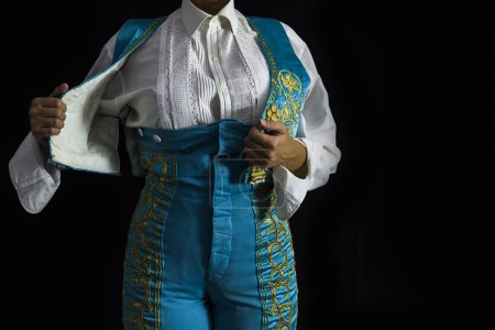 Woman bullfighter by dressing with vest on your back on a black