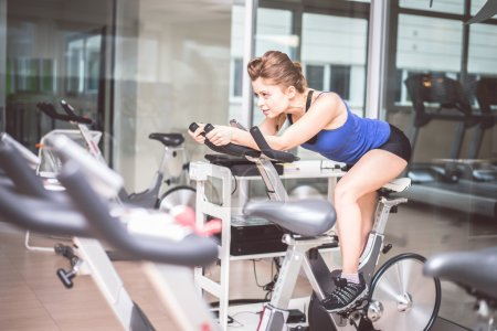 Woman training on bike in a gym