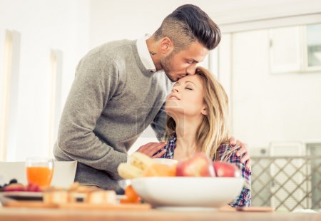 Young couple in love having breakfast at home.