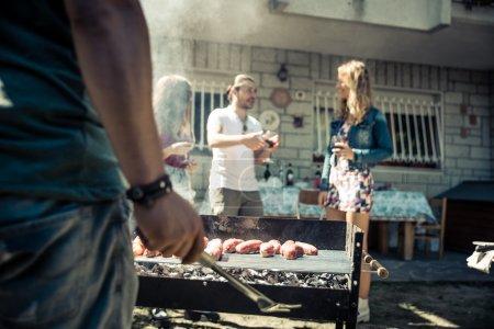 Photo pour Amis dans le jardin à la maison griller la viande et s'amuser - Groupe de personnes à la fête barbecue boire du vin - image libre de droit