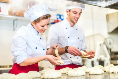 Photo for Two pastry chefs preparing croissants in a confectionery laboratory - Royalty Free Image