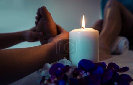 Photo pour Gros plan des pieds de femme et des décorations de saloon de beauté. Esthéticienne massant les pieds. Concept de soins corporels, spa et massages - image libre de droit