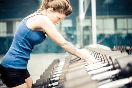 Woman taking dumbbells in a fitness gym
