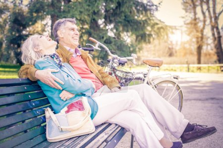 Photo pour Couples gais aînés s'asseyant sur un banc dans un stationnement - deux retraités ayant l'amusement ensemble à l'extérieur - image libre de droit