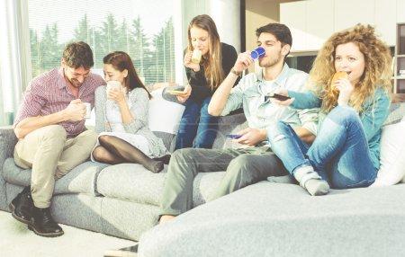 Photo pour Groupe de jeunes gens prenant son petit déjeuner dans le salon - image libre de droit