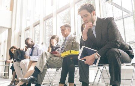 Photo pour Rangée de gens d'affaires en attente pour une entrevue. Notion sur les entreprises et professions - image libre de droit
