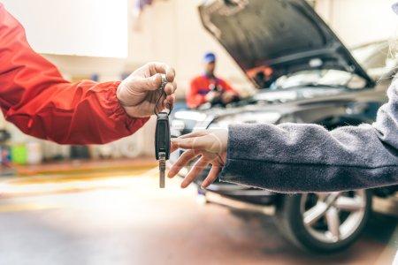 Mechanic handing woman automobile keys