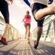 Three runners sprinting outdoors - Sportive people...