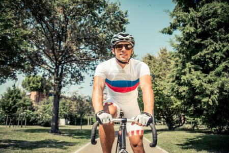 Photo for Athlete cycling in a park - Professional cyclist training outdoors - Royalty Free Image