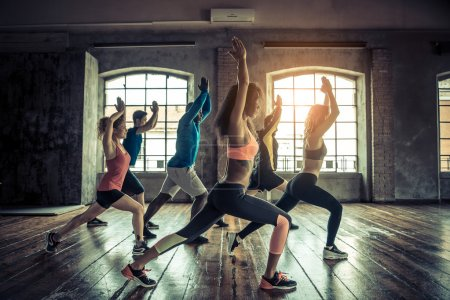Photo for Group of sportive people in a gym training - Multiracial group of athletes stretching before starting a workout session - Royalty Free Image