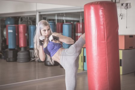 Fighter woman hits the heavy bag
