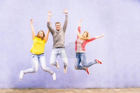 Friends jumping on a blue wall