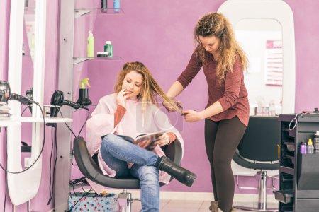 Photo pour Belle jeune coiffeuse donnant une nouvelle coupe de cheveux à la cliente - image libre de droit