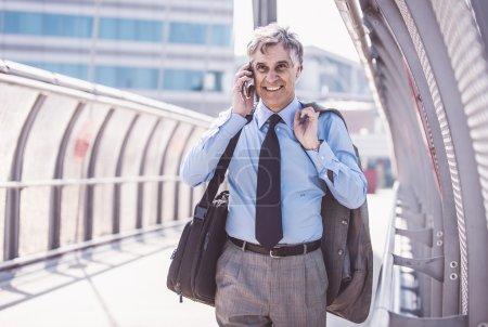 Photo pour Homme d'affaires marchant et parlant au téléphone, concept d'affaires et de professions - image libre de droit