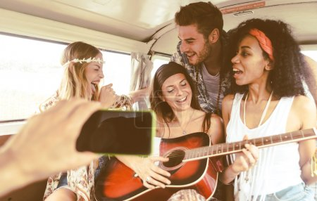 Photo for Hippie friends having fun into a vintage van, playing the guitar and singing songs - Royalty Free Image