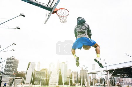 Street basketball player performing an huge rear slam dunk