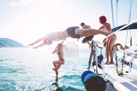 Friends diving in water during boat excursion