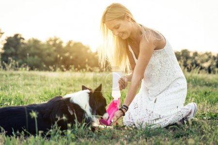 Photo for Beautiful blonde woman playing with her loyal border collie dog - Royalty Free Image