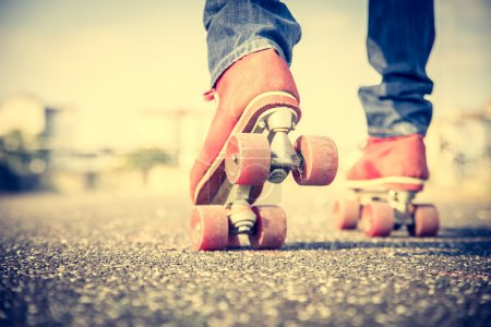 Photo for Cool man with roller skating shoe using his mobile phone - Concepts of youthness,sport,lifestyle and 80s vintage style - Royalty Free Image