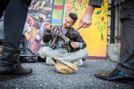 Street artist playing guitar on the streets