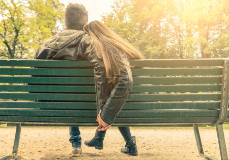 Photo for Couple on a bench - Two lovers sitting on a bench in a park and holding themselves by hands - Concepts of autumn,love,togetherness,relationship - Royalty Free Image