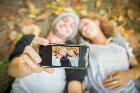 Couple taking selfie in autumn