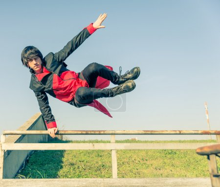 Photo for Parkour athlete jumping over a handrail - Free runner performing tricks in a urban settlement - Parkour,free running,youth,sport and lifestyle concept - Royalty Free Image