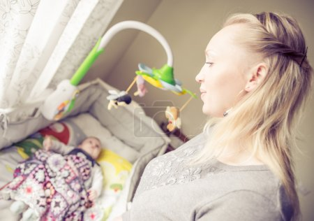 Photo for Mom looking at her son while sleeping - Mother singing a lullaby to her baby - Royalty Free Image