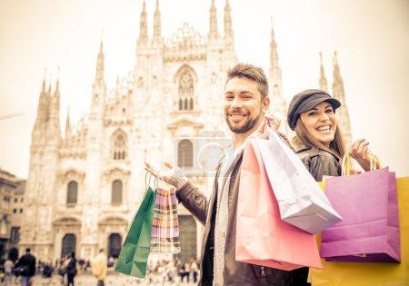 Photo pour Couple achetant lors d'une vente - Homme et femme attrayant tenant des sacs à provisions et s'amusant - humeur automne et hiver - image libre de droit