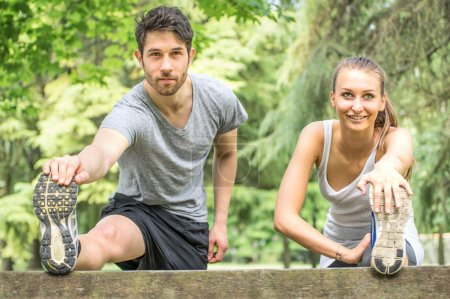 Sporty couple stretching legs outdoors
