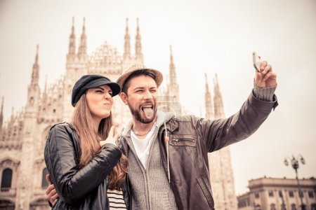 Photo for Happy tourists taking a self portrait with phone in front of Duomo cathedral,Milan - Couple travelling in Italy - Royalty Free Image