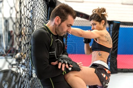 Photo for Woman training martial arts with her coach in the gym - Two mixed martial arts athletes fighting in the cage - Royalty Free Image