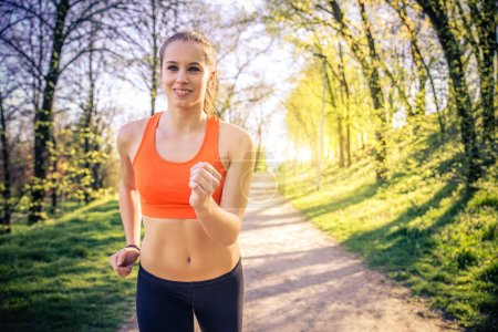 Photo for Young sportive woman training in a park for marathon - Athlete running outdoors at sunset - Attractive girl making sport to lose weight and stay fit - Royalty Free Image