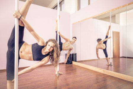 Photo for Couple dancing at pole in a fitness studio - Ballet dancers working out - Pole dancers looking at camera and stretching legs - Royalty Free Image