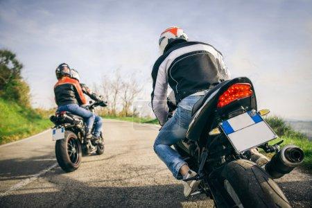 Photo pour Deux motos conduisant dans la nature - Amis conduisant des motos de course avec leurs amies - image libre de droit
