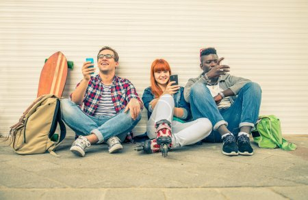 Photo for Group of friends of different ethnics sitting on the street and looking at mobile phone - Young modern hipster people having fun with new technologies - Multiracial group representing the addiction to technology - Royalty Free Image