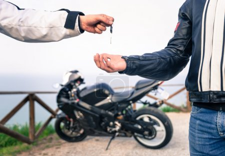Photo for Key exchange. Motorcycle concept. friends exchanging the bike key. - Royalty Free Image