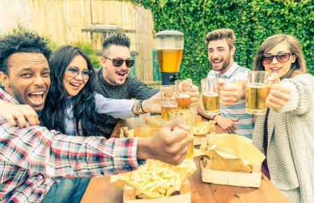 Photo for Group of mult-ethnic friends toasting beer glasses - Happy people partying and eating in home garden - Young active adults in a picnic area with burgers and drinks - Royalty Free Image