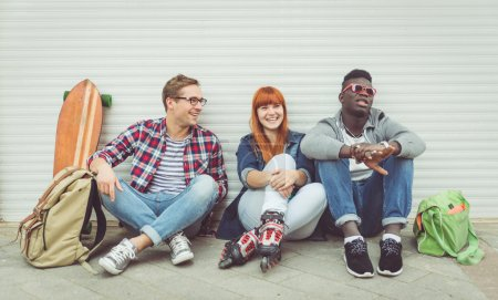 Photo for Three mixed race friends sitting and having fun. concept about people and youth - Royalty Free Image