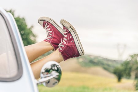 Photo for Woman relaxing in her car while driving in the countryside - Young  cool girl with shoes out of the automobile window to enjoy the view - Royalty Free Image