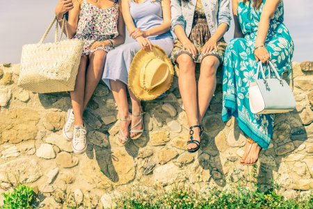 Photo pour Four girlfriends sitting on a wall outdoors with spring and summer dressware - Women meeting and having fun in a countryside - Concepts about friendship,seasonal,lifestyle and shopping - image libre de droit