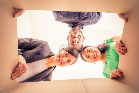 Photo for Group of friends moving to new apartment and unpacking boxes -  Happy people looking inside a box - Royalty Free Image