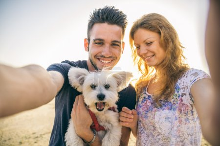 Photo for Portrait of young happy couple with dog taking a selfie - Lovers on a romantic date on the beach at sunset - Royalty Free Image
