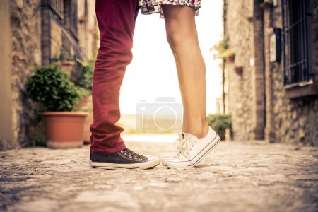 Photo for Couple kissing outdoors - Lovers on a romantic date at sunset,girls stands on tiptoe to kiss her man - Close up on shoes - Royalty Free Image