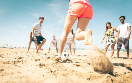group of friends playing soccer on the beach